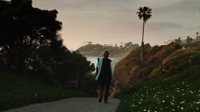 Surfer Walking Down to Beach at Sunset