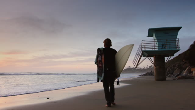 surfer walking on beach at sunset - san diego stock videos & royalty-free footage