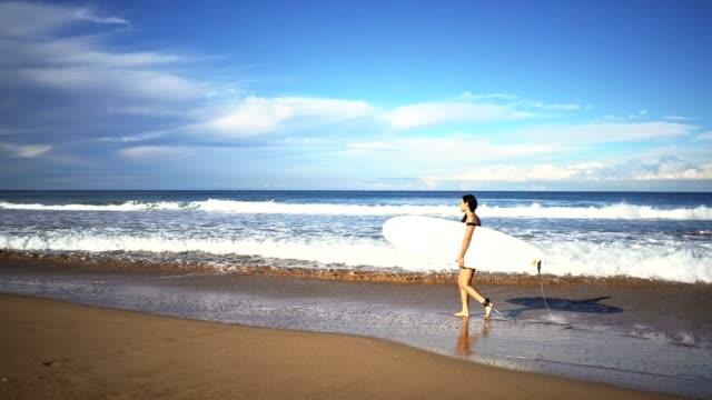 サーファー ビーチの上を歩く - 泡立つ波点の映像素材/bロール