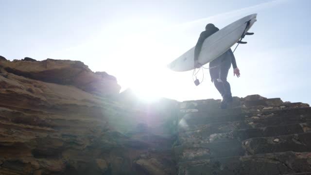 vídeos de stock, filmes e b-roll de a surfer walking up a cliff trail with his surfboard. - slow motion - diving suit