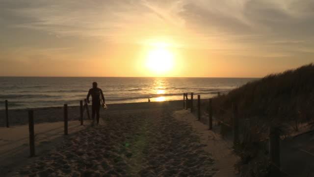 A surfer walks across a beach towards the shoreline.