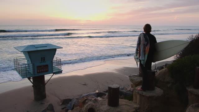 Surfer Watching Ocean at Sunset