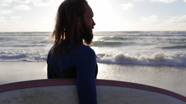 surfer with surfboard looking out over waves and toward horizon on beach in france - introspection stock videos & royalty-free footage