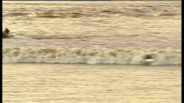 surfers and canoeists ride severn bore england gloucestershire river severn ext various of surfers and canoeists 'riding' severn bore tidal wave... - river severn stock videos & royalty-free footage