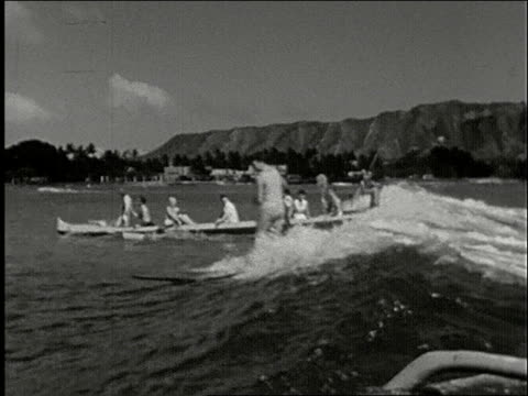 vídeos y material grabado en eventos de stock de surfers and outrigger canoes riding waves, diamond head in background / kayak races wave, man wipes out \ head stand on surfboard with dachshund dog... - honolulu