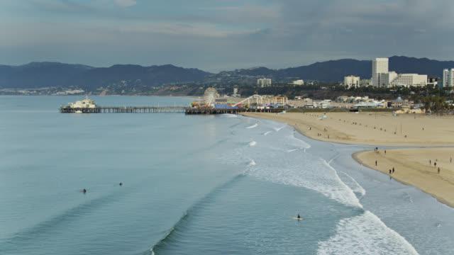 vídeos y material grabado en eventos de stock de surfistas y caminantes en santa monica beach temprano en la mañana - drone shot - santa monica los ángeles