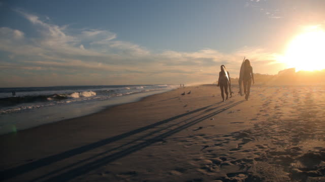 surfers carrying surfboards on beach - queens stock-videos und b-roll-filmmaterial