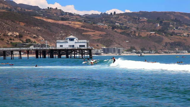 surfers enjoy high tide in malibu beach near the pier, pacific ocean, california - malibu stock videos & royalty-free footage