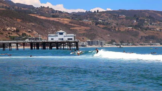 stockvideo's en b-roll-footage met surfers enjoy high tide in malibu beach near the pier, pacific ocean, california - malibu