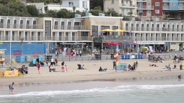 surfers enjoy the waves at boscombe beach bournemouth on saturday - bournemouth stock-videos und b-roll-filmmaterial