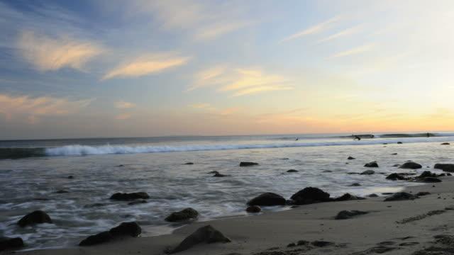surfers gather under beautiful sunset