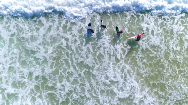 stockvideo's en b-roll-footage met surfers gaan uit de zee - golf sport