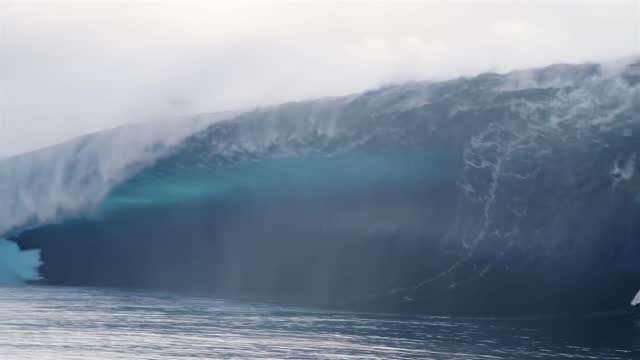 surfers hugged their boards and paddled over an enormous wave in the waters off the island of tahiti in french polynesia on may 23. photographer... - french polynesia stock videos & royalty-free footage