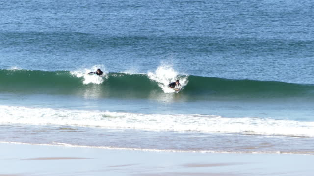 surfers in carcavelos beach, near lisbon, on the first week of a three-stage reopening plan for the activities disrupted by the covid-19 coronavirus... - カスカイス点の映像素材/bロール