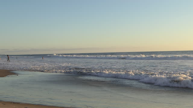 surfers in the ocean on surfboards, moonlight beach in encinitas, california, sunset, southern california. - relaxation stock videos & royalty-free footage