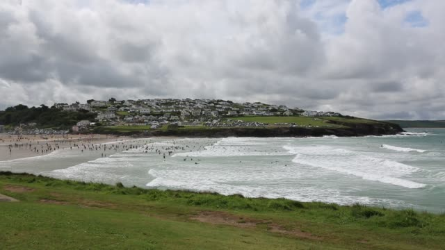 Surfers in the swell at Polzeath, Cornwall, UK.