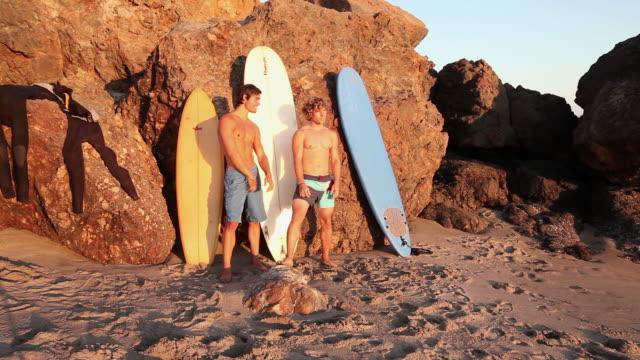 surfers on the beach - サーフパンツ点の映像素材/bロール