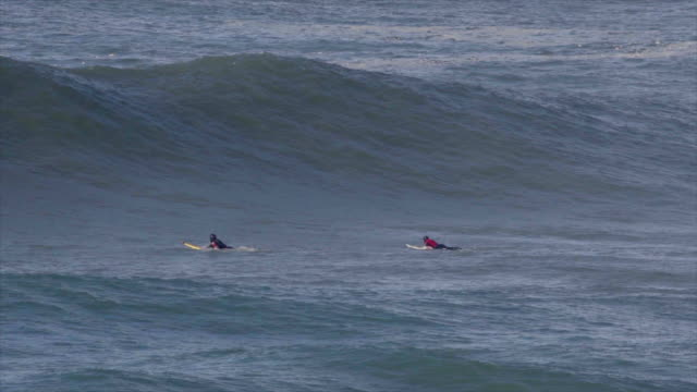 surfers paddle out over waves while surfing huge waves. - slow motion - pagaiare video stock e b–roll