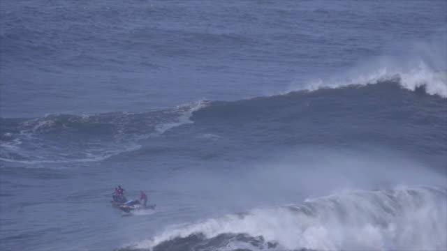 vídeos de stock, filmes e b-roll de surfers paddle out over waves while surfing huge waves. - slow motion - apavorado