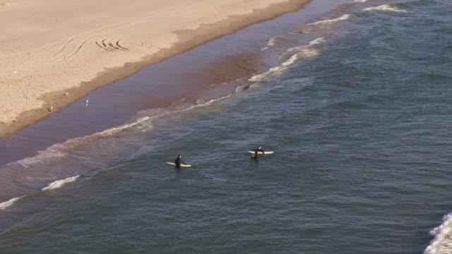 surfers returning to shore - costa dell'oregon video stock e b–roll