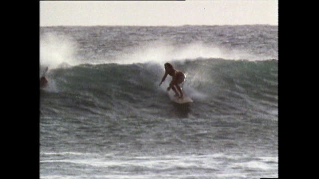 surfers ride the waves at waikiki beach in 1983 - getting away from it all stock videos & royalty-free footage