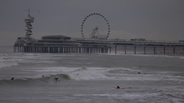 surfers ride the waves in the north sea, the scheveningen pier in the background on october 19, 2020 in the hague, the netherlands. for a few days... - silver coloured stock videos & royalty-free footage