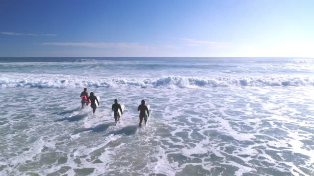 surfers running into the sea - surfboard stock videos and b-roll footage
