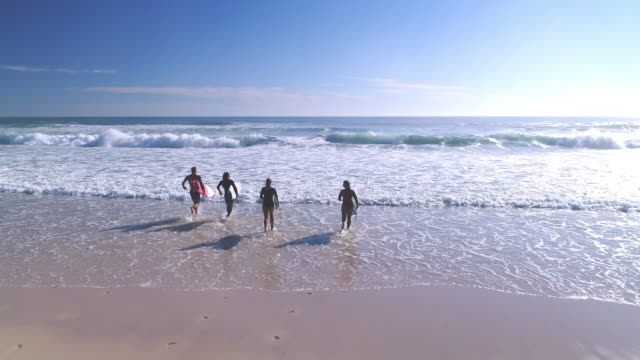 surfers running into the sea - queensland stock videos & royalty-free footage