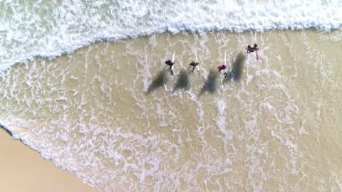 stockvideo's en b-roll-footage met surfers loopt in de zee - surf