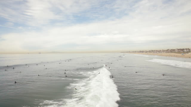 ws surfers surfing at beach / huntington beach, california, united states     - huntington beach california stock videos and b-roll footage