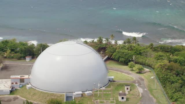 WS ZO AERIAL POV Surfers surfing in sea, BONUS Nuclear Reactor in background / Rincon, Puerto Rico, United States