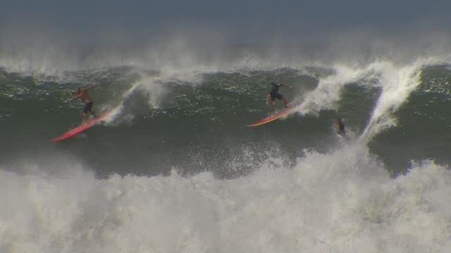 stockvideo's en b-roll-footage met surfers take on the challenge of the big waves on the north shore of oahu in the hawaiian island - oahu