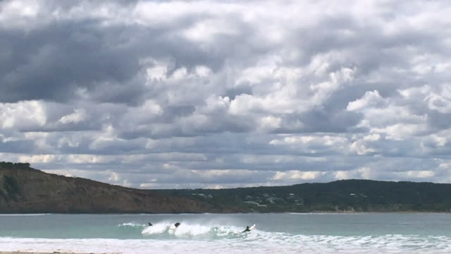 surfers tumbling in the waves at Point Roadknight on a stormy Autumn day