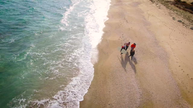 Surfers walking down the beach 4K