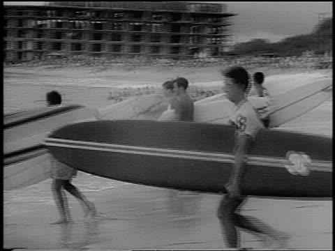 B/W 1966 PAN surfers walking into ocean with surfboards / Hawaii / newsreel