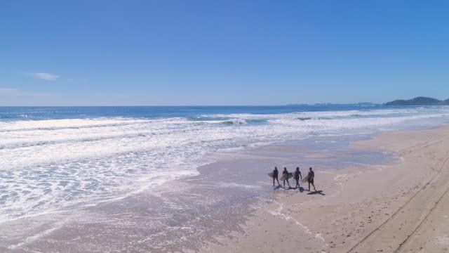 vidéos et rushes de surfers marchant sur la plage - quatre personnes