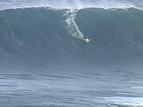 surfing a huge wave at Jaws, Maui