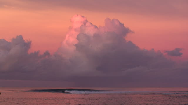 Surfing in Tahiti. Pink clouds just after sunset