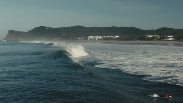 surfing in the ocean. sun reflecting in waves - nicaragua stock videos & royalty-free footage