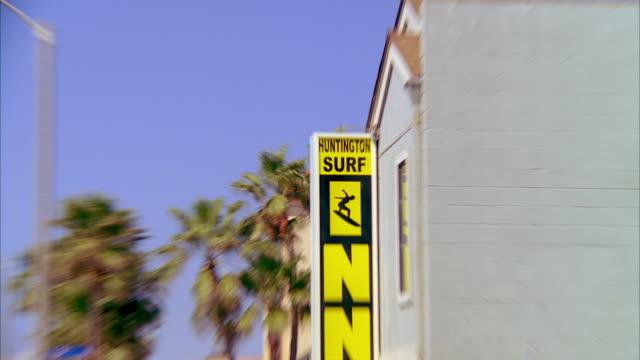 WS ZI ZO Surfing sign on building, traffic on road / Laguna, California, USA