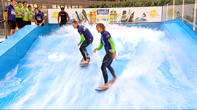 surfing simulator set up near liverpool street station; england: london: liverpool street station: ext surfers surfing in surfing simulator surfer... - city von london stock-videos und b-roll-filmmaterial