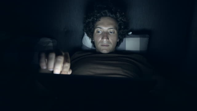 surfing the net in bed at night. - wasting time stock videos & royalty-free footage