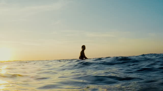 vídeos de stock, filmes e b-roll de surfing woman in atlantic ocean on summer evening on surfboard at sunset - frança