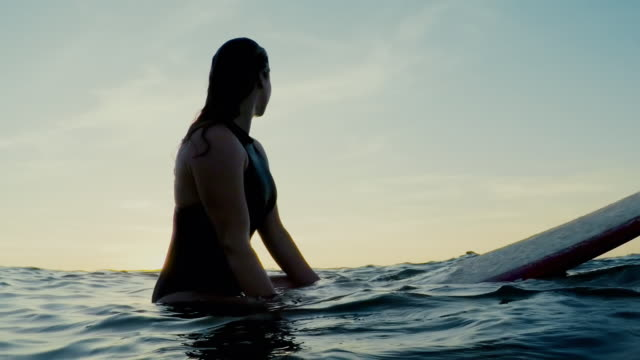 surfing woman in atlantic ocean on summer evening on surfboard at sunset - pagaiare video stock e b–roll