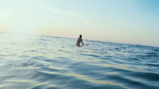 vídeos de stock e filmes b-roll de surfing woman in atlantic ocean on summer evening on surfboard at sunset - anticipation