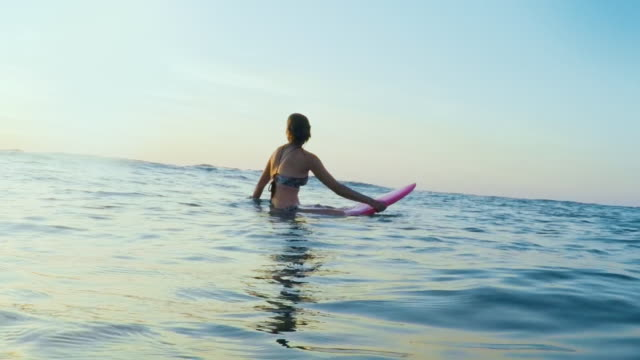 vídeos y material grabado en eventos de stock de surfing woman in atlantic ocean on summer evening on surfboard at sunset - tabla de surf
