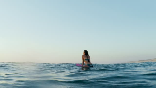 Surfing woman in Atlantic ocean on summer evening on surfboard at sunset