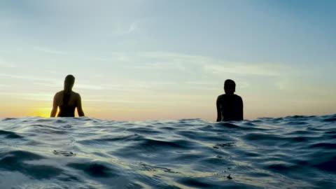 vídeos y material grabado en eventos de stock de surfing women in atlantic ocean on summer evening on surfboard at sunset - surf