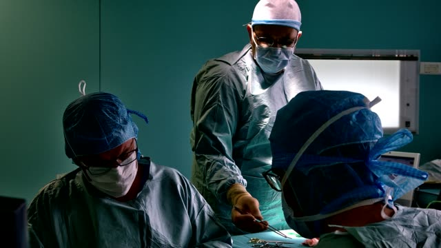 vidéos et rushes de surgeon and his assistant operating - bloc