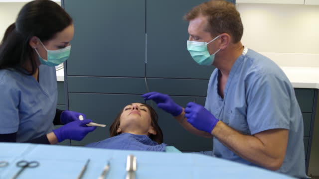 stockvideo's en b-roll-footage met surgeon and medical assistant preparing a mid adult woman for a plastic surgery - plastische chirurg